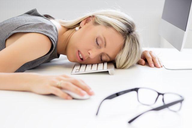 Сонная женщина за компьютером