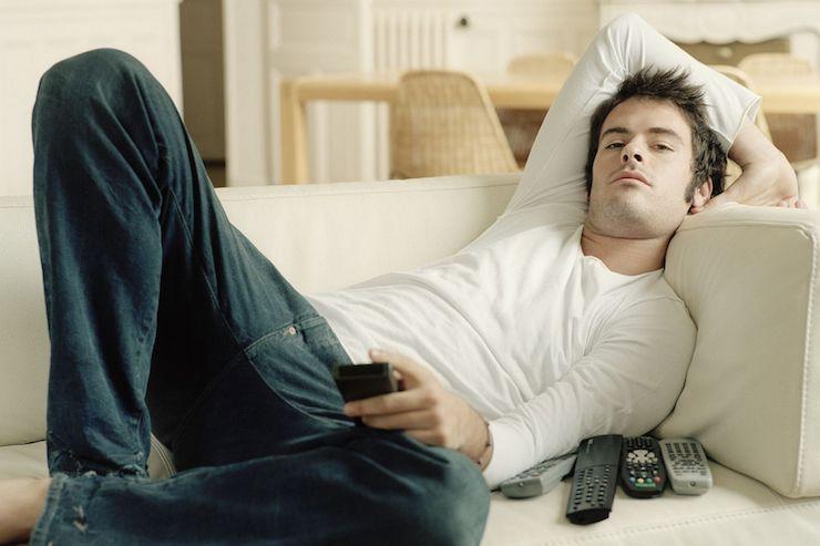 мужчина лениво смотрит телевизор