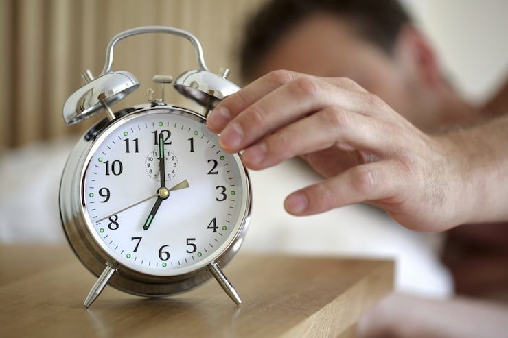 мужчина выключает будильник